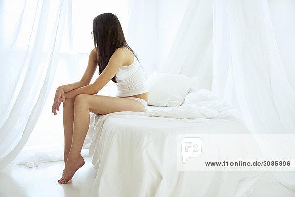 Eine junge Frau sitzend am Rande des ein Bett Blick aus einem Fenster