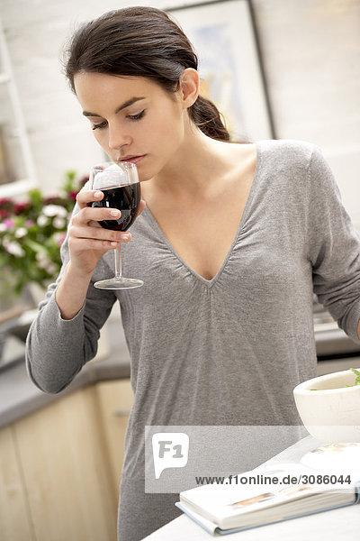 junge Frau junge Frauen sehen Buch Wein trinken Taschenbuch multitasking Kochrezept Rezept
