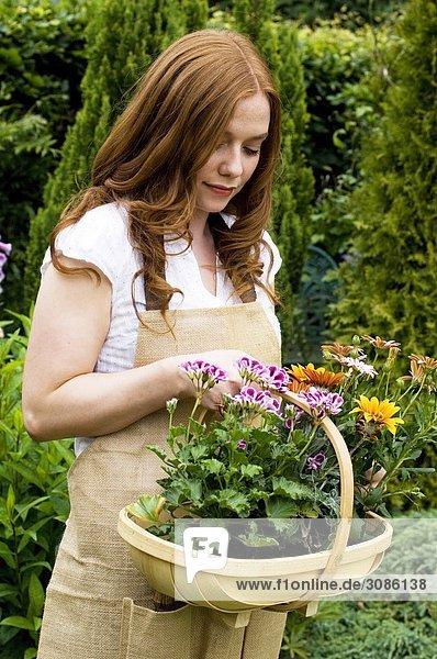 Eine Frau mit einen Korb von Pflanzen