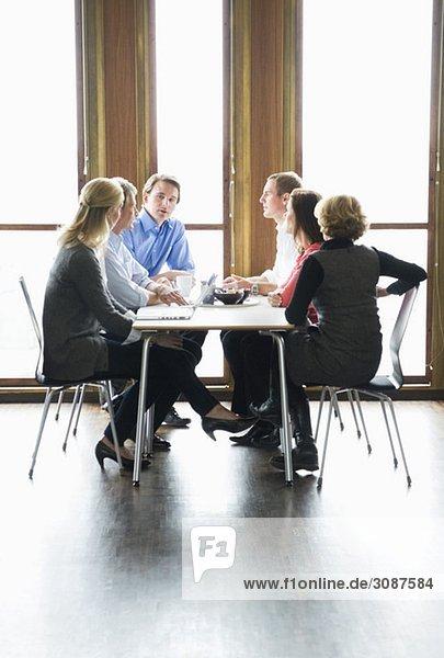 Sechs Leute sitzen am Tisch und reden.