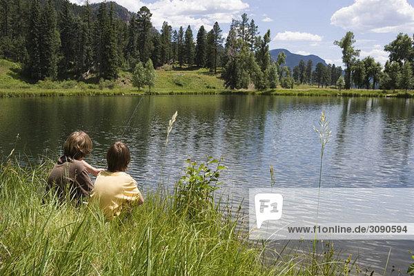 Two boys fishing at the edge of a lake  Durango  Colorado  USA