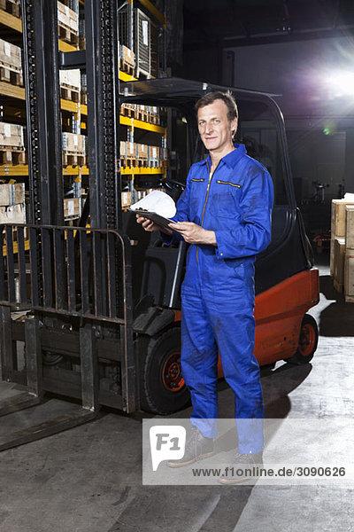 Ein Handwerker mit einer Checkliste in einem Metallteilelager