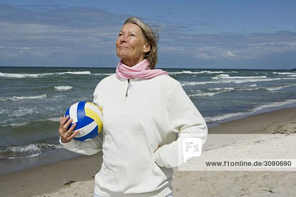 Eine ältere Frau hält einen Fußball.