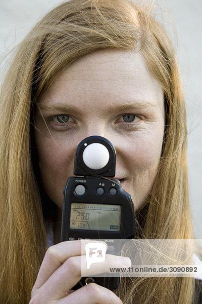 Eine Frau hält einen Belichtungsmesser vor ihr Gesicht.