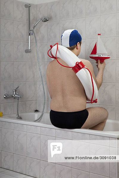 A man wearing racing briefs and a life preserver sitting on the edge of a bathtub  indoors