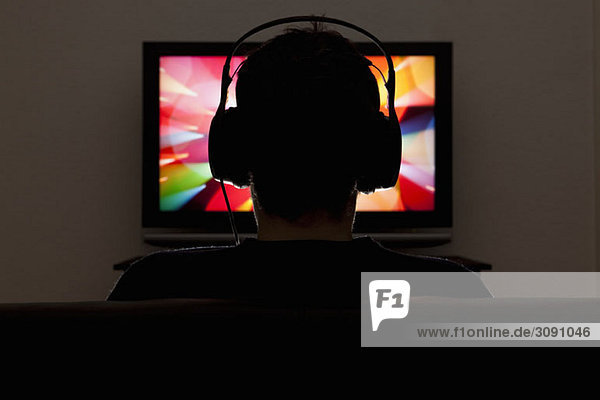 A man wearing headphones and watching television
