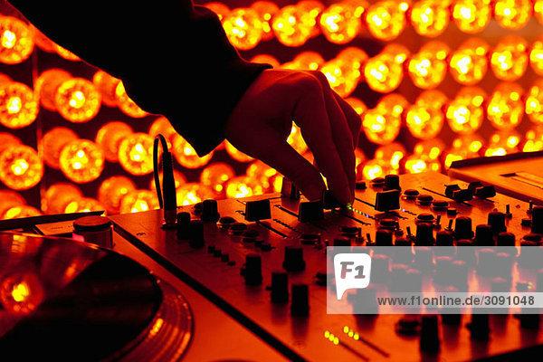 Ein DJ  der die Lautstärke an einem Soundmixer in einem Nachtclub anpasst. Ein DJ, der die Lautstärke an einem Soundmixer in einem Nachtclub anpasst.