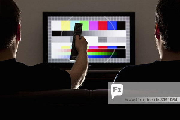 Two men watching a test pattern on a television