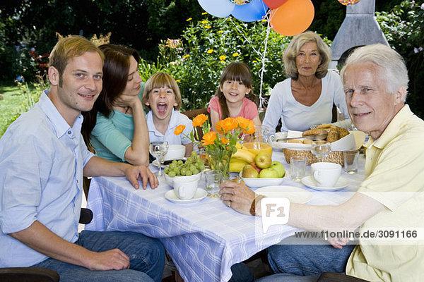 Eine Mehrgenerationen-Familie beim Frühstück im Freien