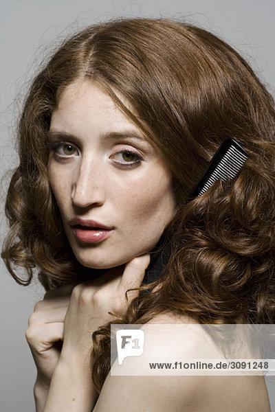 Porträt einer jungen Frau  die ihr Haar kämmt