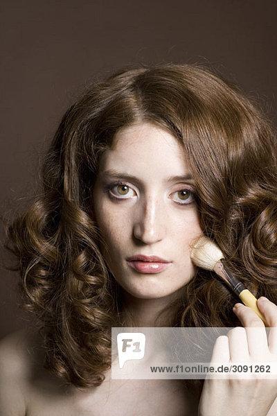 Porträt einer jungen Frau  die Gesichtspuder aufträgt