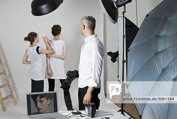 Fotograf,  Model und Maskenbildner am Set eines Modeshootings