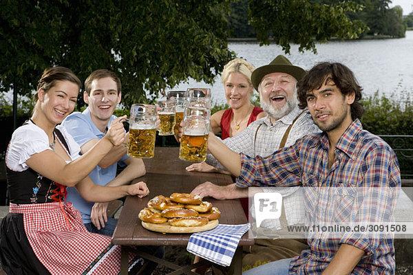 Fünf Personen in einem Biergarten Toastgläser