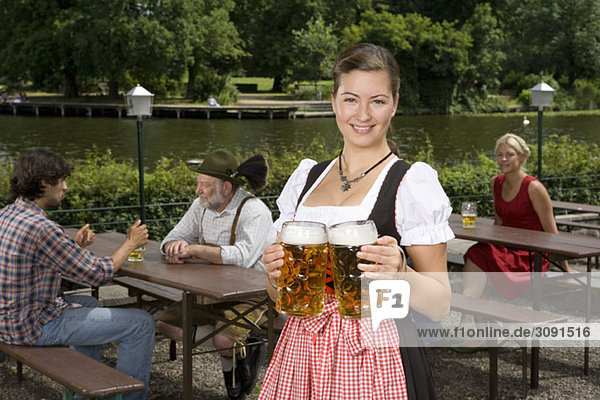 Eine traditionell gekleidete Deutsche serviert Bier im Biergarten Eine traditionell gekleidete Deutsche serviert Bier im Biergarten