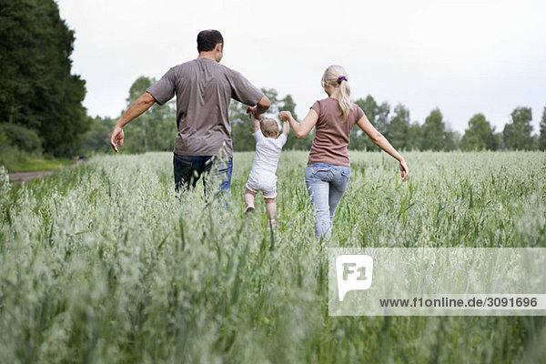 Eine Familie  die durch ein Feld geht.