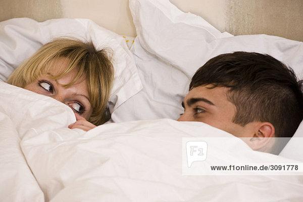 Ein junges Paar im Bett mit hochgezogener Bettdecke