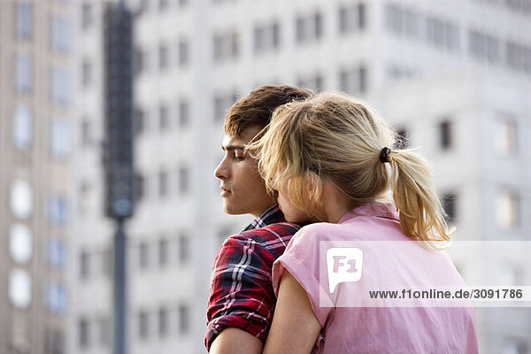Ein junges Paar  das sich in einer städtischen Umgebung umarmt.
