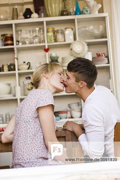Ein junges Paar  das sich mit einer Erdbeere küsst.