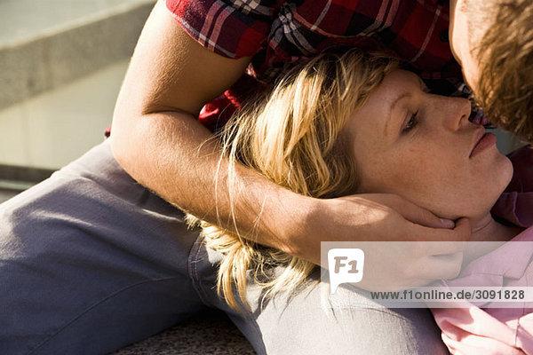 Ein junger Mann  der den Kopf einer jungen Frau in seinem Schoß hält.