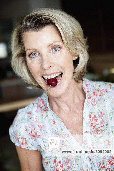 Senior Woman with Cherry between teeth