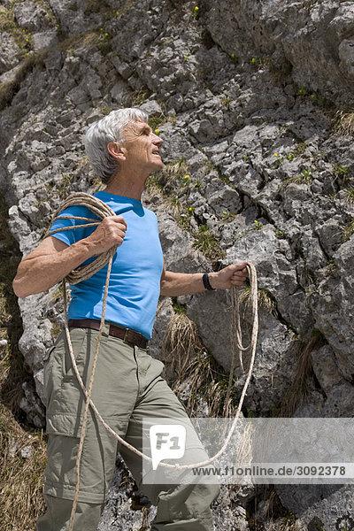 Senior mit Kletterseil am Fels