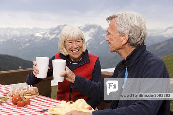 Seniorenpaar beim Essen in den Bergen