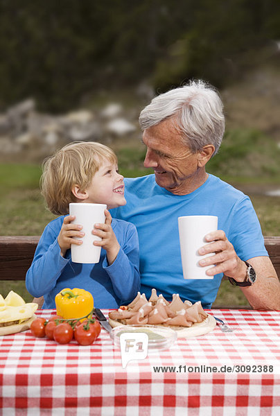 Großvater  Enkel beim Essen in den Bergen