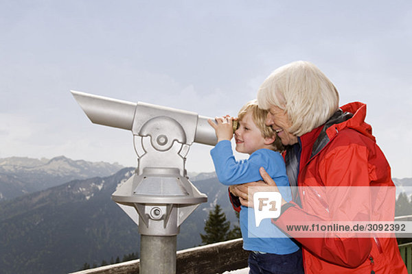 Junge  Oma schaut durchs Teleskop.