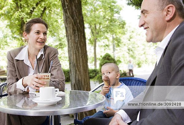 Geschäftspaar mit Sohn im Außencafé