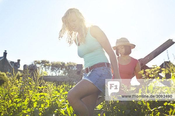 zwei Mädchen  die auf ein Feld gehen.