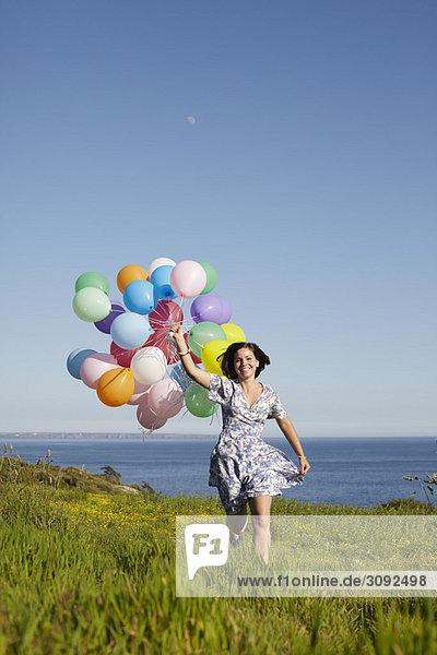 Ein Mädchen  das mit Luftballons rennt.