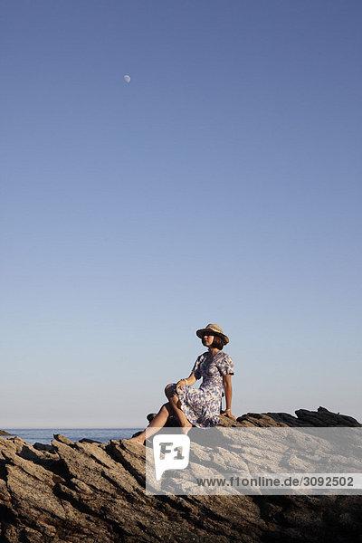 Mädchen auf Felsen am Meer sitzend