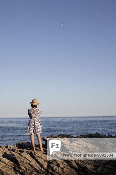 Mädchen auf Felsen am Meer stehend