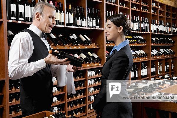 zeigen Geschäftsfrau Wein Flasche Kellner