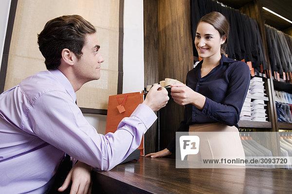 Frau bezahlen mit Kreditkarte in einem Bekleidungsgeschäft