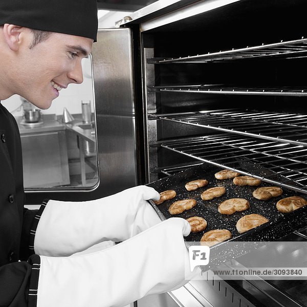 Chef taking out a tray of cookies from an oven