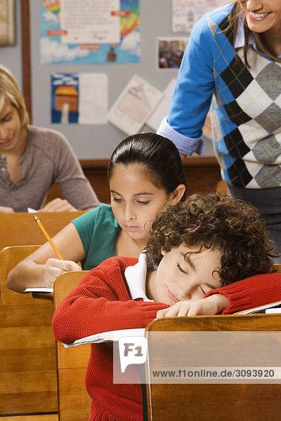 Studierende mit Jugendlicher schlafen in einem Klassenzimmer