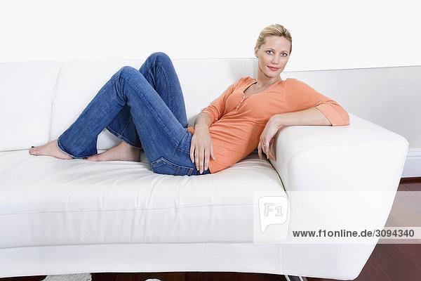 liegend liegen liegt liegendes liegender liegende daliegen Frau lächeln Couch zurücklehnen