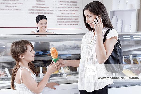 Frau geben Eis an ihre Tochter und sprechen auf einem Mobiltelefon