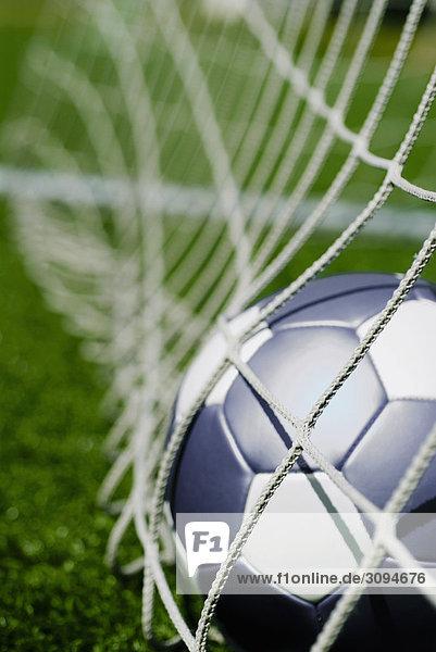 Nahaufnahme von einem Fußball im Netz Nahaufnahme von einem Fußball im Netz