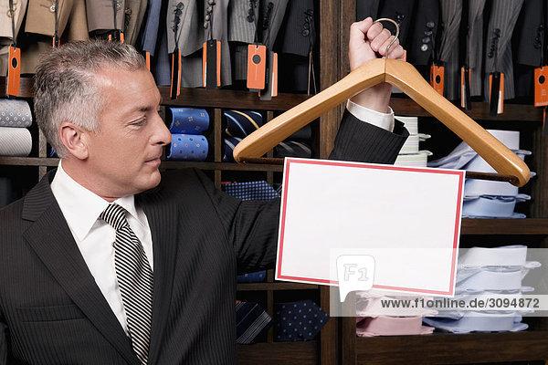 Unternehmer hält ein Kleiderbügel mit leeren Schild in einem Bekleidungsgeschäft