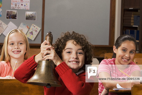 Schoolboy holding a bell with two schoolgirls sitting behind him in a classroom