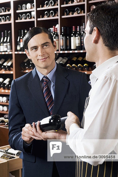 Sales clerk showing a wine bottle to a customer