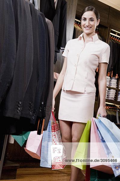 Frau hält Einkaufstaschen in einem Bekleidungsgeschäft