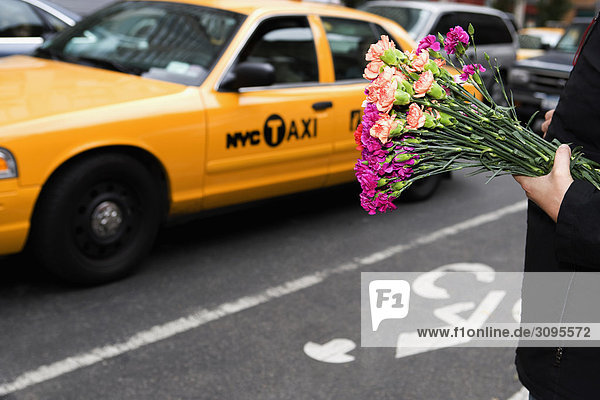 Man holding bunch of flowers in a market  28 Street  New York City  New York State  USA