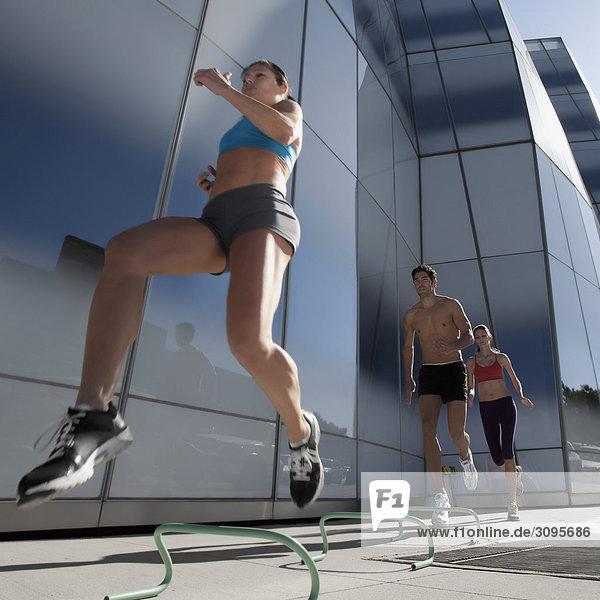 Untersicht Mann und zwei Frauen Hürdenlauf