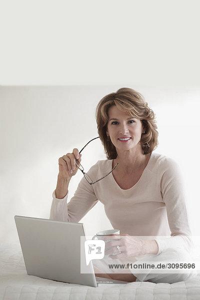Frau Tasse Notebook arbeiten halten Kaffee