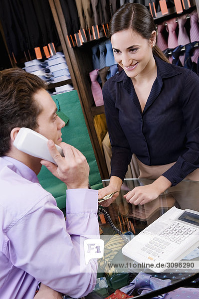 Salesman talking on the telephone in a clothing store