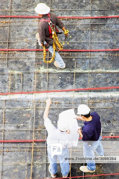 Erhöhte Ansicht von zwei Architekten stehend mit einem Bauarbeiter auf einer Baustelle