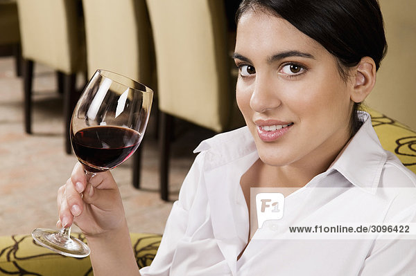 Businesswoman drinking wine and smiling